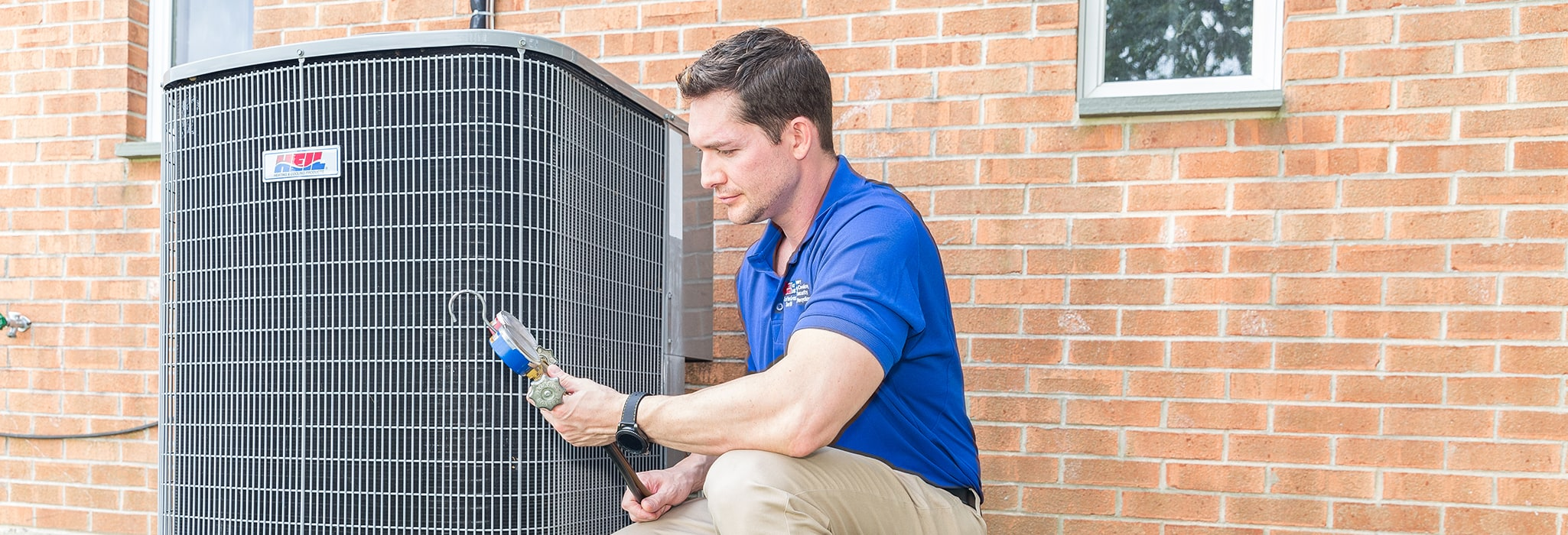 Burns & McBride team member installing a new air conditioning unit outside.