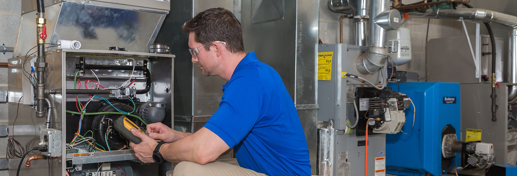 Burns & McBride technician using a multimeter to check the electrical components of a furnace.