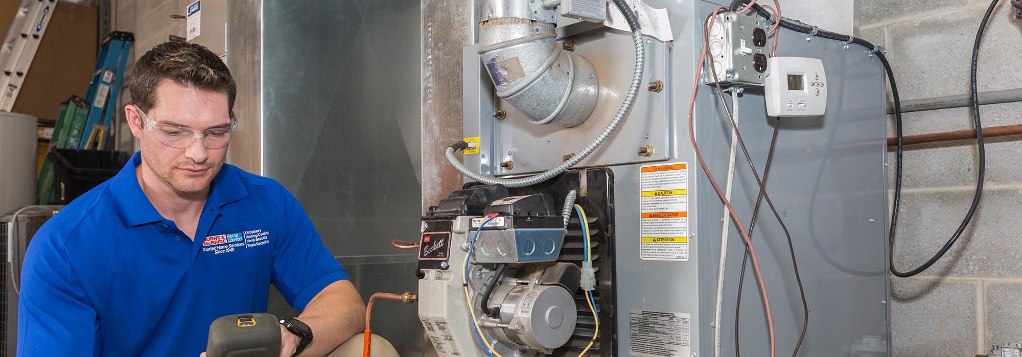 Burns & McBride technician servicing an HVAC unit in Wilmington, DE.