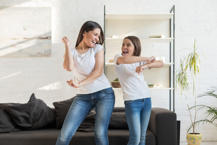 Mom with kid girl dancing in living room. They are happy to save money when upgrading their HVAC system.