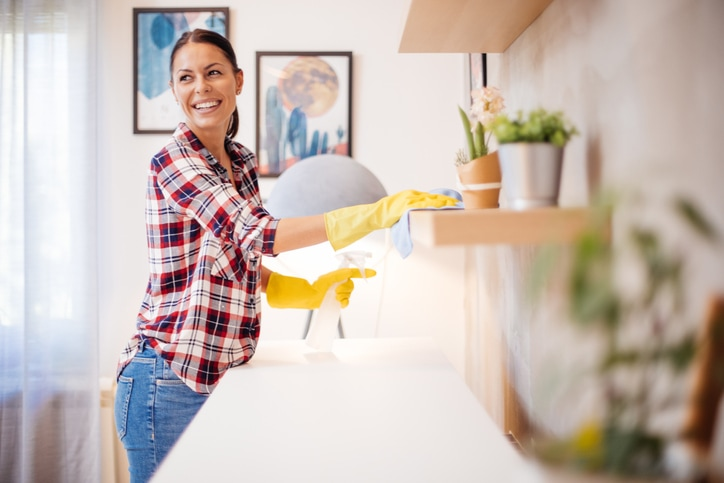 Beautiful Caucasian young woman in casual clothes with yellow gloves cleaning furniture in living room at home.